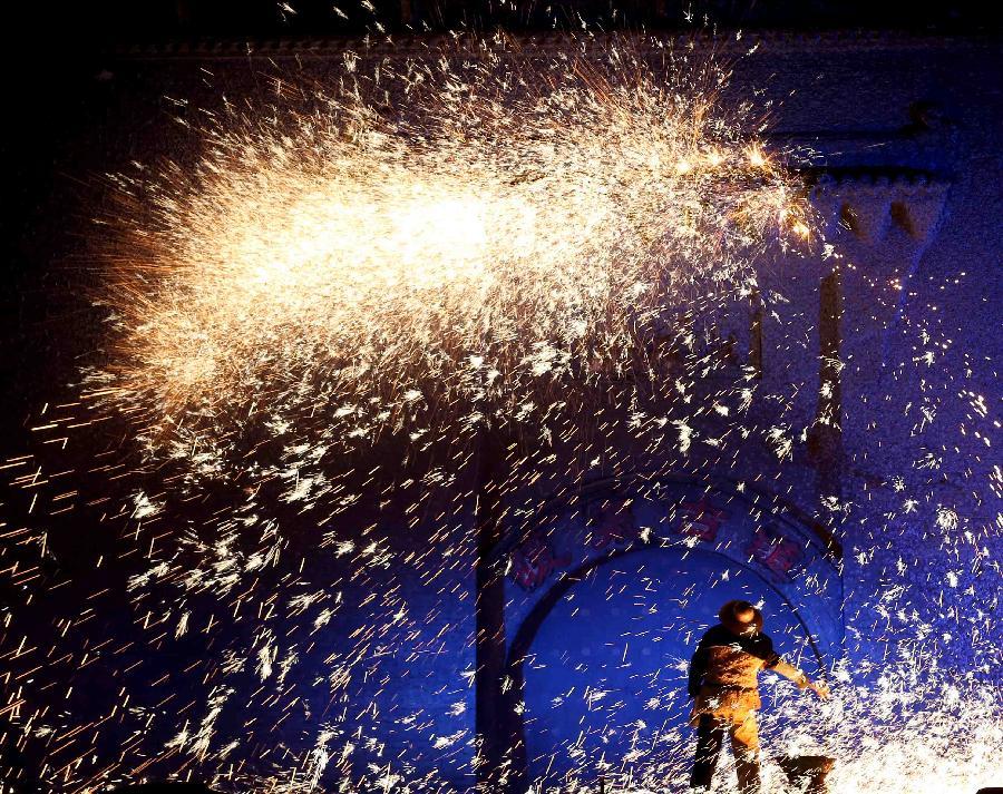 2月23日,民俗艺人在河北蔚县暖泉镇表演打树花。  当日,火树银花大型实景民俗表演在河北省蔚县暖泉镇举行,通过歌舞、打树花等传统民俗表演欢庆中华民族传统节日元宵节。河北省非物质文化遗产打树花发源于蔚县暖泉镇。铁匠们将炼成的铁水扬抛甩溅在城墙上,铁水遇冷迸溅四射,形成万朵火花,犹如枝繁叶茂的树冠,因此被称为树花。新华社记者 陈建力 摄